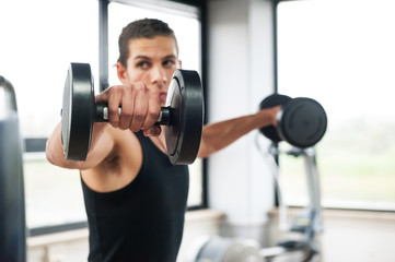 Young man exercising with dumbbells in a gym, focus on weight.