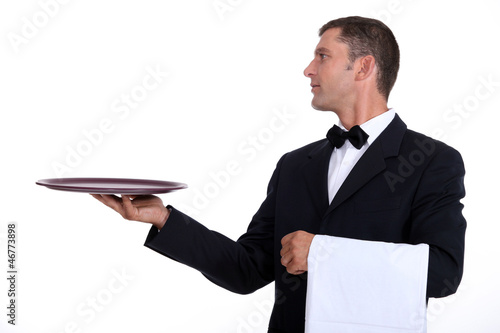 A waiter holding an empty tray
