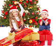 Children with gift box near Christmas tree.