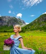 Lovely woman in  blue dress with  basket of flowers