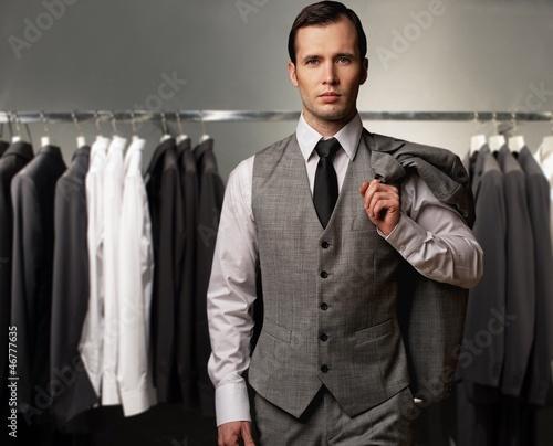 biznesmen-w-klasycznej-kamizelce-przeciw-rzedowi-kostiumy-w-sklepie