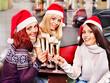 Women in santa hat drinking champagne.