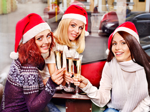 Women in santa hat drinking champagne.