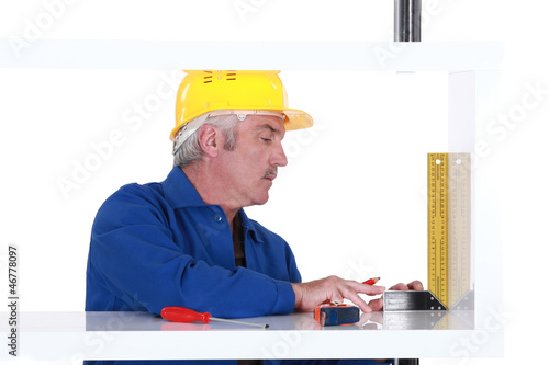 mature carpenter taking measurements