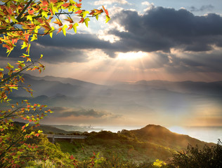 The sun setting over mountains with nice maple