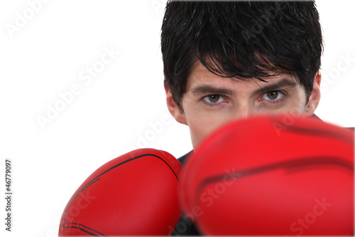 Boxer hiding behind his boxing gloves