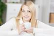blonde frau genießt eine tasse tee