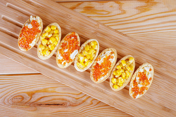 Tartlets with red caviar and corn