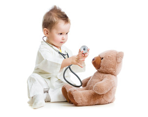 kid or child playing doctor with stethoscope and teddy bear isol