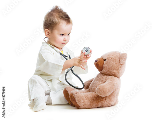 Fototapeta kid or child playing doctor with stethoscope and teddy bear isol