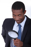 Businessman using magnifying glass