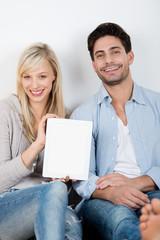 glückliches paar zeigt tablet-pc