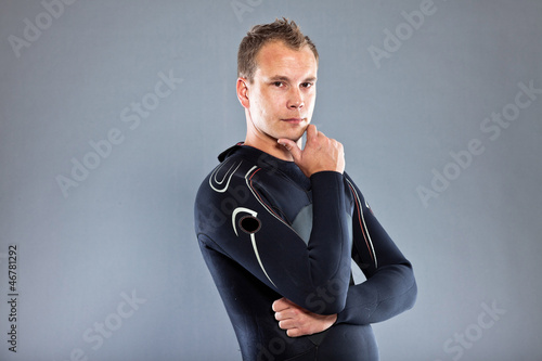 Confident man with short hair wearing wetsuit. Kite surfer.