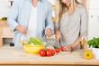 paar schneidet salat in der küche