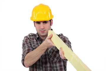 Construction worker examining a piece of wood