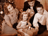Family with children  receiving gifts under Christmas tree.