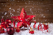 candle,holly,baubles,star and ribbons in snow before wood