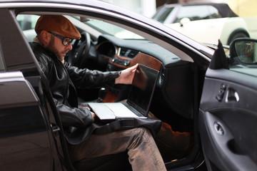 Mann sitzt im Auto mit Laptop