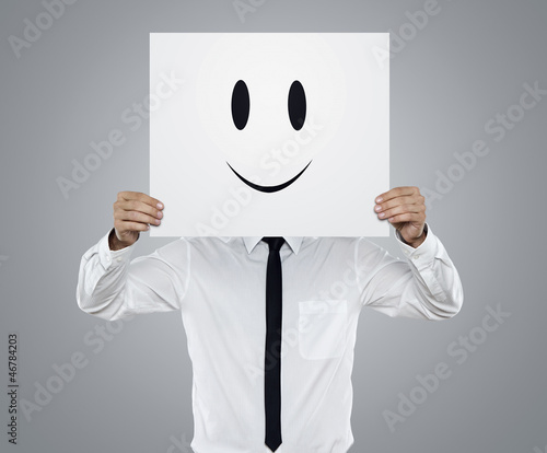 Young businessman holding card with a happy face on it
