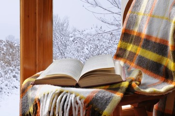 Book on a chair in winter, near the window
