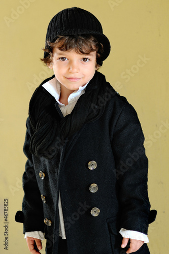 portrait of little stylish boy outdoors in a coat