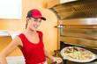 Frau schiebt die Pizza in den Ofen