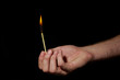 Hand holding burning match stick on black background