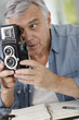Senior photographer holding vintage camera