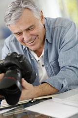 Photographer in office looking at camera screen