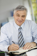 Portrait of senior businessman writing on agenda