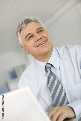 Portrait of senior businessman in office working on laptop