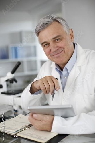 Portrait of scientist in lab using digital tablet