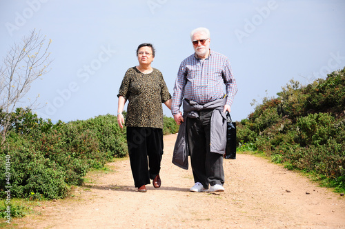 lovely senior couple walking on a path