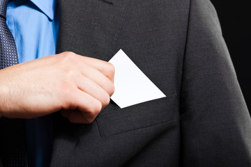 Business man puts a business card in the poket