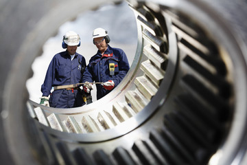 engineering and industry workers seen through giant gear axle