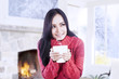 Attractive girl warming at fireplace hold coffee