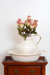 Old bowl and jug on a stand with fake roses