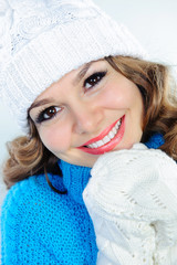 Smiling woman in knitted sweater, hat, and gloves
