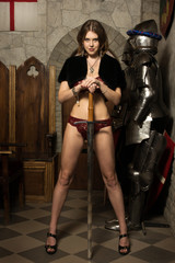 Sexy woman with a sword in a medieval castle interior