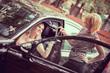 Car dealer giving keys of a new car to head customer
