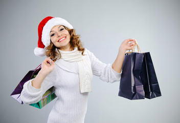 Beautiful young girl in Santa hat with shopping bags