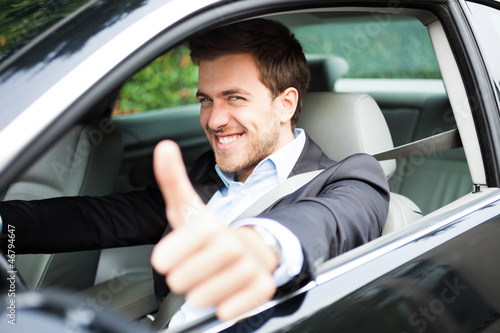 Portrait of an happy man on his car