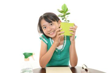 植木鉢を持ち微笑む女の子