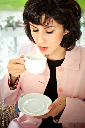 women drinking  coffee in café smiling