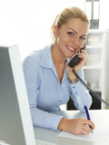 Female office assistant has a call and makes notes at the office