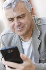 Portrait of senior man using smartphone in town