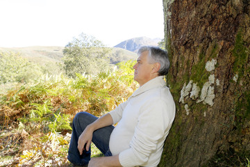 Senior man relaxing in nature, leant againt tree