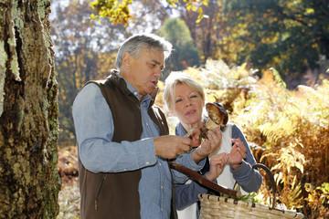 Senior couple in forest holding ceps mushrooms