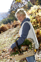 Senior woman in forest holding basket of mushrooms