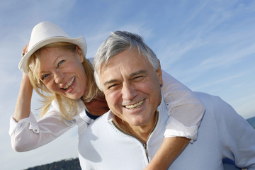 Portrait of cheerful senior couple having fun at the beach